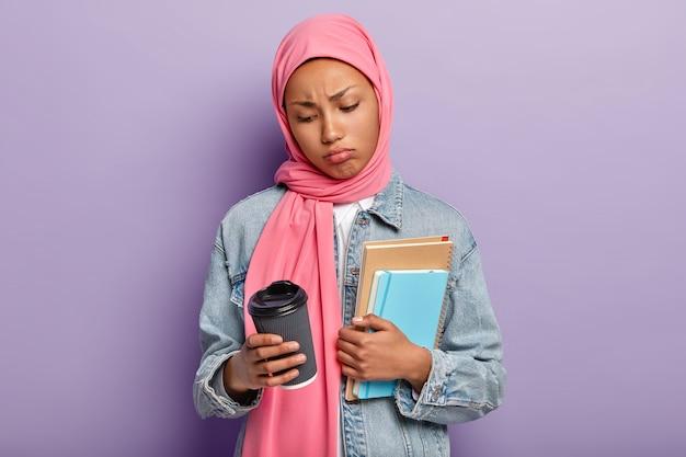 Insoddisfatta donna di razza mista triste tiene quaderni a spirale, caffè da asporto, beve bevande calde, indossa velo rosa sulla testa e giacca di jeans, non ha voglia di studiare, isolato su un muro viola