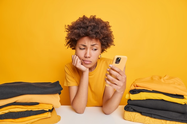 Dissatisfied sad woman feels tired after folding clothes looks attentively at smartphone checks newsfeed leans at table surrounded by two stacks of yellow and black folded laundry poses indoor