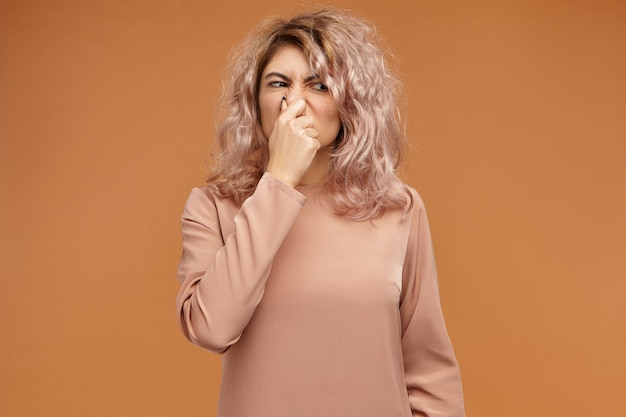 Giovane donna alla moda insoddisfatta che vomiterà a causa dell'intollerabile puzza dei calzini sporchi. ragazza divertente che fa smorfie e pizzica il naso, trattenendo il respiro