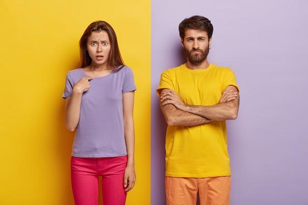 不満の不機嫌そうな無精ひげを生やした男は腕を組んで、憤慨している若い女性は自分自身を指しています 無料写真