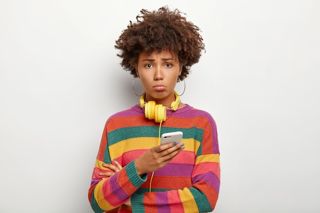 Dissatisfied teenager with curly hairstyle, uses smart phone, feels lonely and upset, dressed in striped sweater