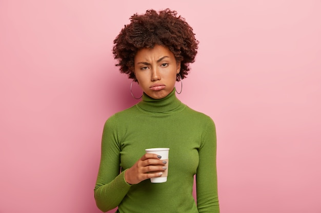 Dissatisfied tired african american woman holds takeaway coffee, tries to refresh after hard work, wears green polo neck sweater, sighs from tiredness, feels overworked