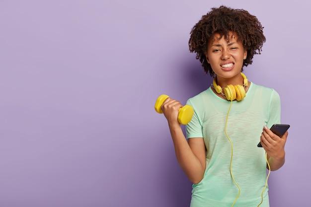 불만족스러운 피곤한 여자는 스포츠 의류를 입고, 케틀벨로 손을 들고, 얼굴을 능글 맞게 웃으며, 헤드폰에 연결된 핸드폰을 보유하고 있습니다.