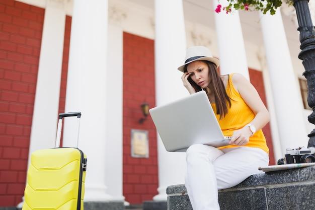 여행 가방을 머리에 붙이고 도시 야외에서 노트북 컴퓨터 작업을 하는 모자를 쓴 불만족스러운 여행자 관광 여성. 주말 휴가에 해외 여행을 하는 소녀. 관광 여행 라이프 스타일.