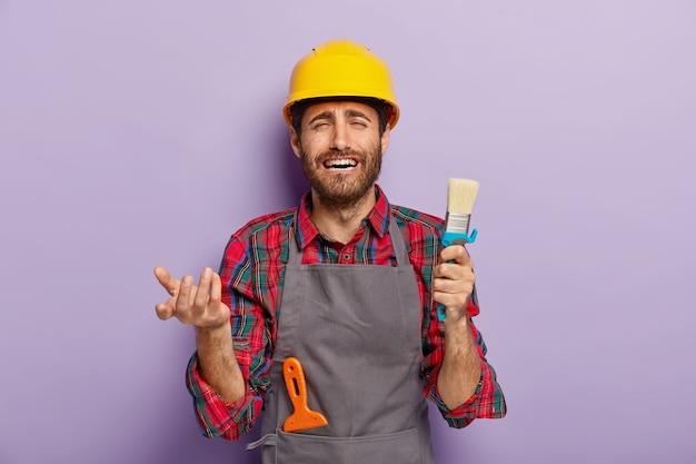 不満を持った不幸な男性画家は、絵筆を持って、仕事に慌てて、家での修理で忙しく、黄色いヘルメットと灰色のエプロンを着ています。建設作業員が建築ツールでポーズをとる