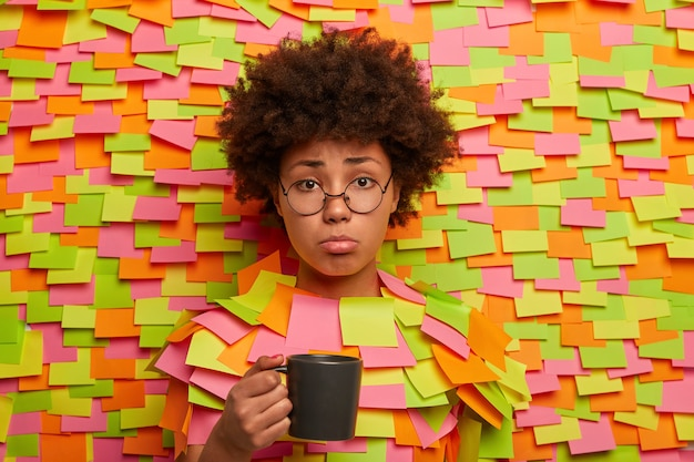 Dissatisfied unhappy woman holds cup of tea, feels tired of work, discontent to have some problems, has pity expression, sticks out head in paper wall with colored stickers. fatigue female student