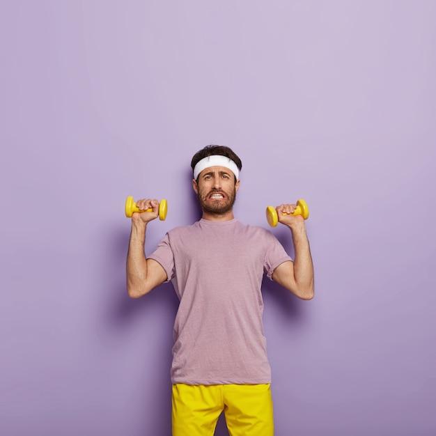 不満を持った無精ひげを生やした男は、腕を上げ、上腕二頭筋を鍛え、白いヘッドバンドとアクティブウェアを着用し、ダンベルを握り、疲れた表情をし、歯を食いしばります
