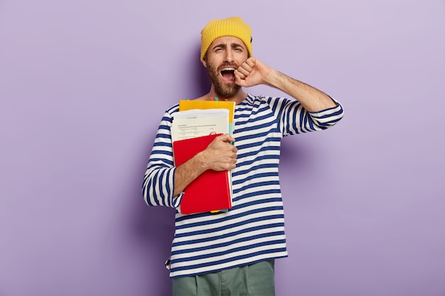 Недовольный небритый молодой человек зевает от усталости, сонный и истощенный, держит руку у открытого рта, держит бумаги с блокнотом и учебником.
