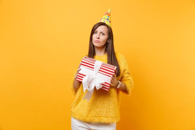 贈り物と赤い箱を保持している誕生日パーティーハットで不満を持って動揺している若い女性、明るい黄色の背景に孤立して祝うプレゼント。人々の誠実な感情、ライフスタイルのコンセプト。広告エリア。