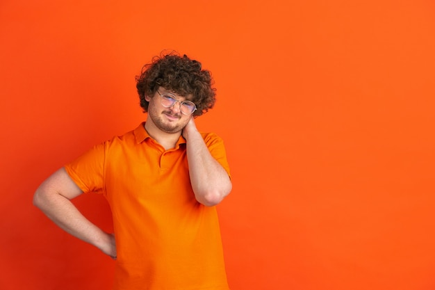 Dissatisfied with something. caucasian young man's monochrome portrait on orange  wall. beautiful male curly model in casual style.