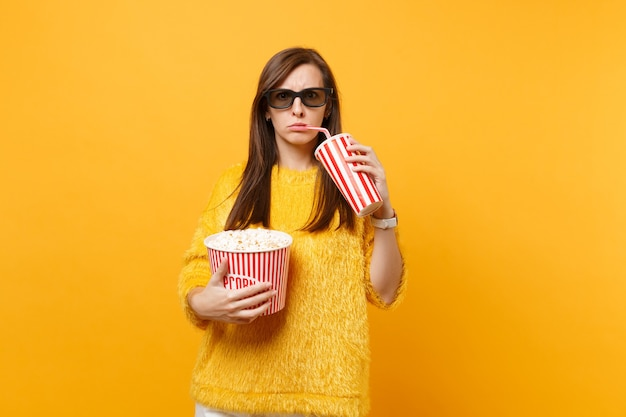 Dissatisfied woman in 3d imax glasses watching movie film holding bucket of popcorn, drinking cola or soda from plastic cup isolated on yellow background. people sincere emotions in cinema, lifestyle.