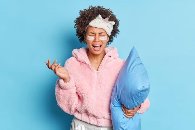 불만족 한 여성이 파자마 수면 마스크를 입은 절망에서 울고 눈 아래에 하이드로 겔 패치를 적용하고 부드러운 베개가 파란색 벽 위에 고립 된 침대에 간다