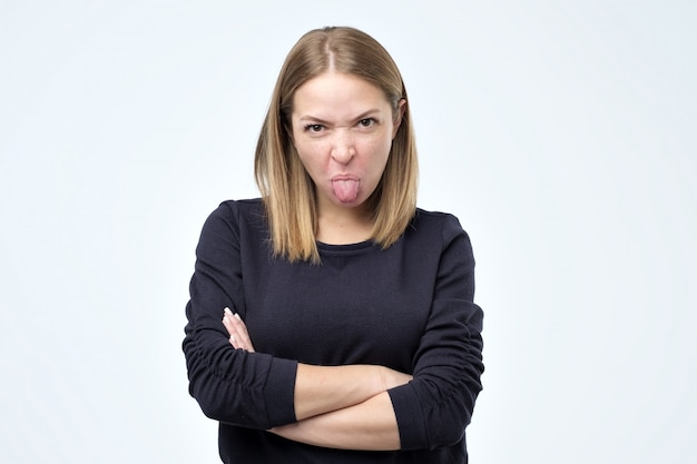 Dissatisfied woman frowns face, has disgusting expression, shows tongue