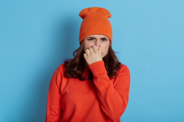 Dissatisfied woman frowns face, lady in cap and casual jumper holds nose because of bad smell