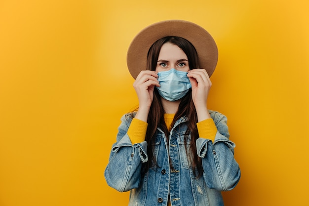 Dissatisfied woman in hat protects face with mask, thinks abot risk of epidemic disease, has virus infection, looks sadly at camera. concept health and safety, n1h1 coronavirus, virus protection