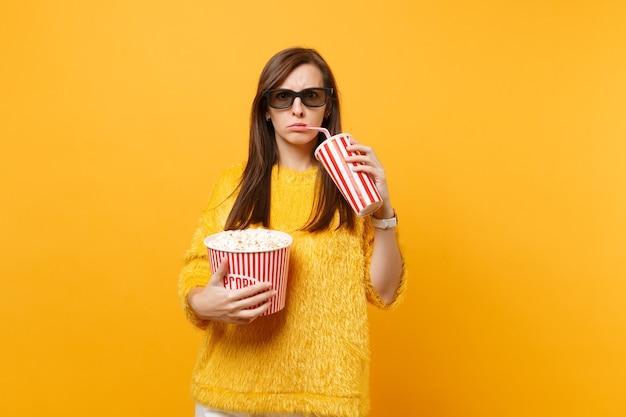 3d 아이맥스 안경을 쓴 불만족스러운 여성은 팝콘 양동이를 들고 노란색 배경에 격리된 플라스틱 컵에서 콜라나 소다를 마시는 영화를 보고 있습니다. 영화, 라이프 스타일에서 사람들은 진실한 감정.