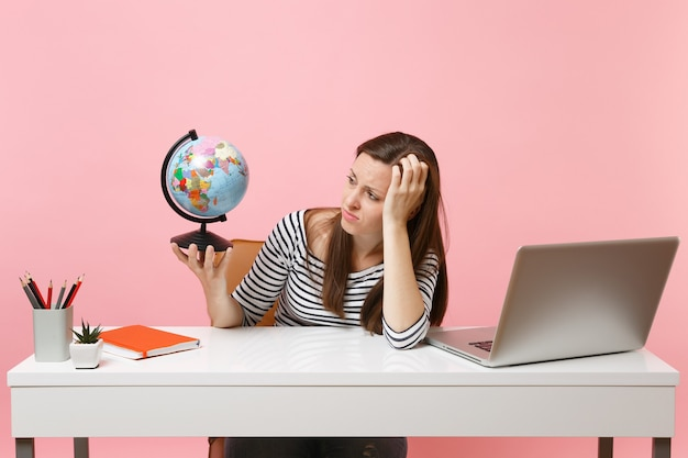 不満のある女性が座っている間、休暇の計画に問題がある地球を持って手に寄りかかって、ラップトップでオフィスで働く
