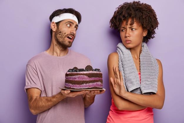 Недовольная женщина делает отказ, просит не предлагать сладкое, сердито смотрит на мужа, который держит вкусный торт.