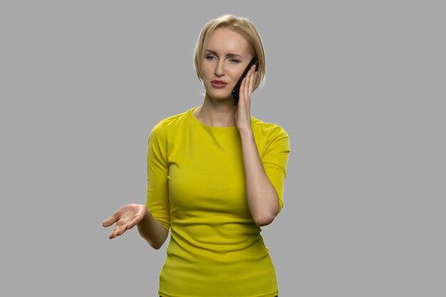 Недовольная женщина разговаривает с кем-то по мобильному телефону. несчастная блондинка разговаривает по мобильному телефону и жестикулирует рукой.
