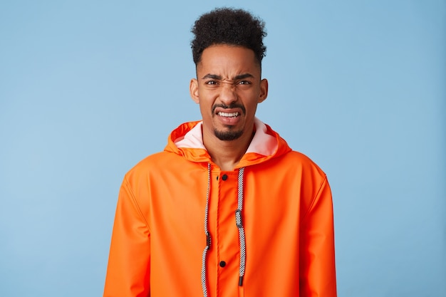 Dissatisfied young african american dark skinned guy wears in orange rain coat, feels very upset, frowns and looks with disgust, stands.