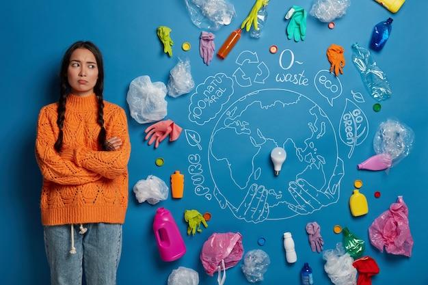 La giovane donna asiatica insoddisfatta tiene le braccia conserte, si sente infelice e preoccupata per i problemi ambientali o naturali, indossa un maglione arancione lavorato a maglia