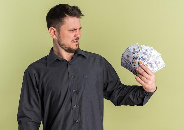 Недовольный молодой блондин красивый мужчина держит и смотрит на деньги