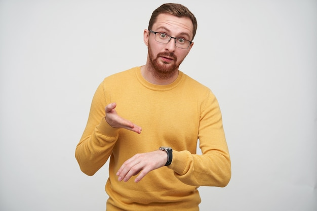 Dissatisfied young brown haired bearded guy in eyewear pointing indignantly on his with wristlet watch, being discontented that someone is late, isolated