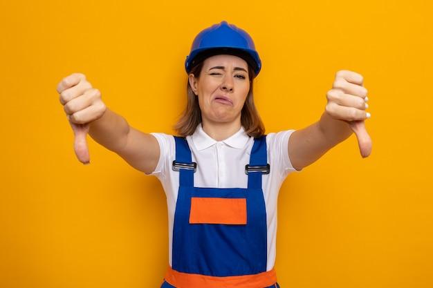 オレンジ色の壁の上に立って親指を下に示す建設制服と安全ヘルメットの不満の若いビルダーの女性