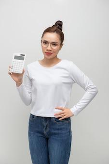 白い壁に隔離されたポーズの白いシャツで不満の若いビジネス女性