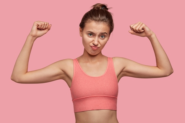 Dissatisfied young caucasian woman raises hands, being discontent with muscles, wears top, goes in for sport, isolated over pink wall. people, healthy lifestyle and motivation concept.