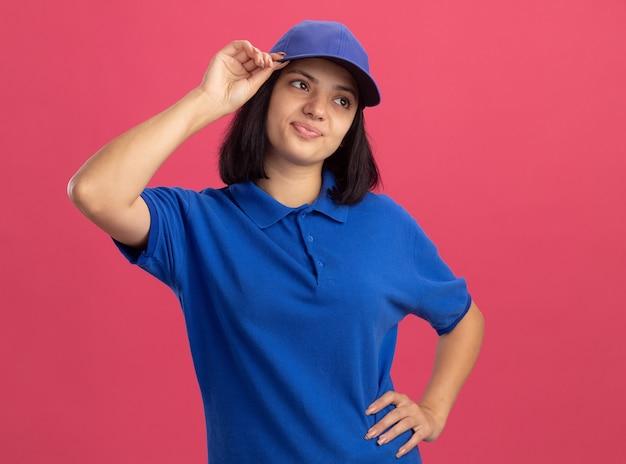 Giovane ragazza insoddisfatta delle consegne in uniforme blu e cappuccio che osserva da parte in piedi perplesso sopra il muro rosa