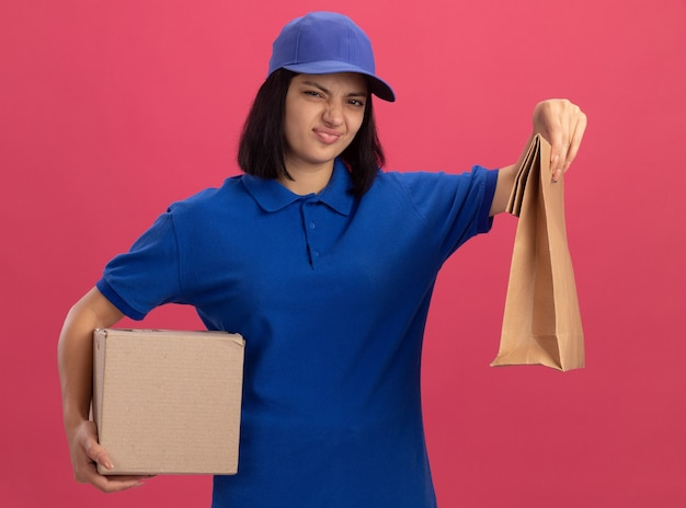 Недовольная молодая доставщица в синей форме и кепке, держащая бумажный пакет и картонную коробку, смотрит, изгибая рот, стоя над розовой стеной