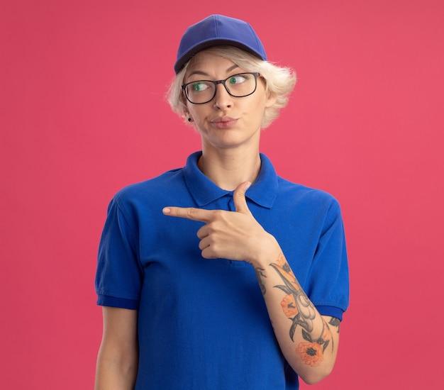 Недовольная молодая женщина-доставщик в синей форме и кепке, смущенно глядя в сторону, указывая указательным пальцем в сторону, стоя над розовой стеной
