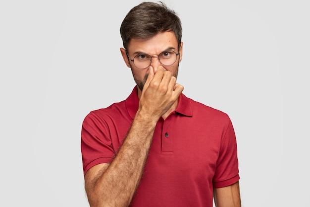 Недовольный молодой эмоциональный мужчина позирует у белой стены