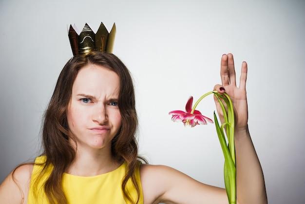 黄色のドレスを着た不満の少女はピンクの花を1つ持っています、世界女性の日の贈り物は好きではありません