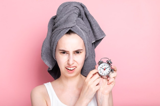 Dissatisfied young girl shows on alarm clock, overslept on pink