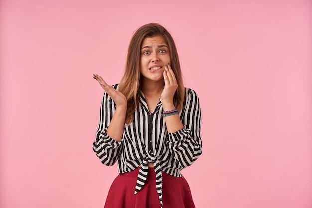 Giovane femmina bruna dagli occhi verdi insoddisfatta che tiene la mano sul viso con il broncio, indossa una camicia a righe e gonna rossa mentre posa sul rosa