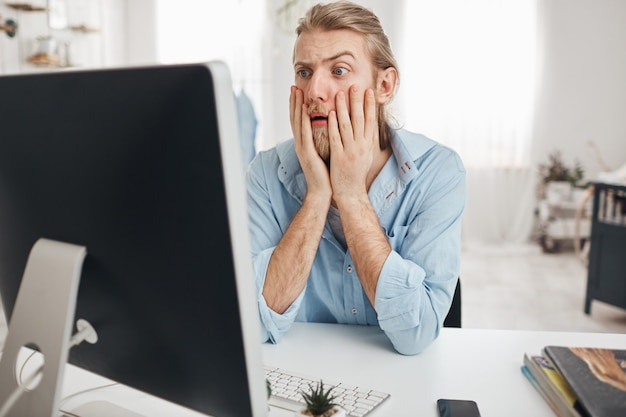 Dissatisfied young male manager looking with bugged eyes and astonishment, shocked by financial report, leaning on elbows while sitting at table in front of computer screen during hard working day