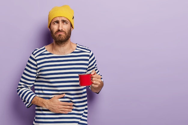 Dissatisfied young man has stomachache, frowns with discontent, holds cup of hot beverage, wears yellow hat, striped sailor jumper