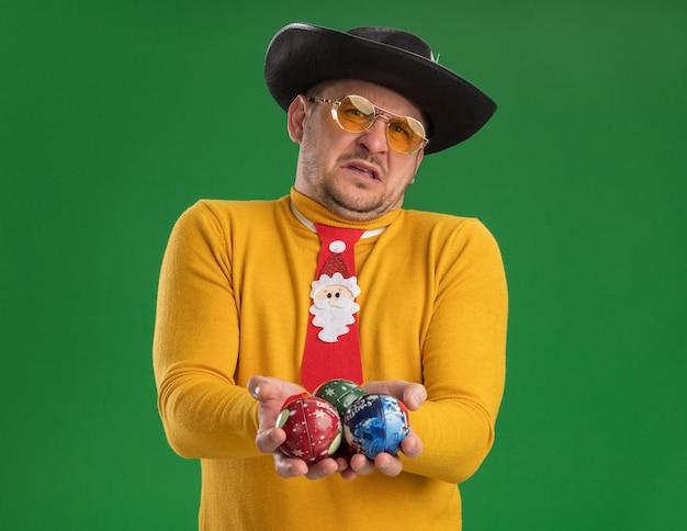 Недовольный молодой человек в желтой водолазке и очках с забавным красным галстуком, держащий игрушки для елки с отвращением на лице, стоит у зеленой стены