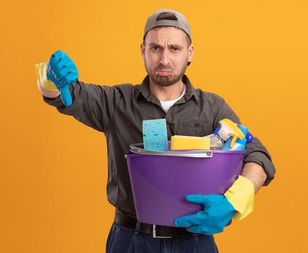 Giovane insoddisfatto che indossa abiti casual e berretto in guanti di gomma che tengono secchio con strumenti di pulizia che mostrano i pollici giù in piedi sopra la parete arancione