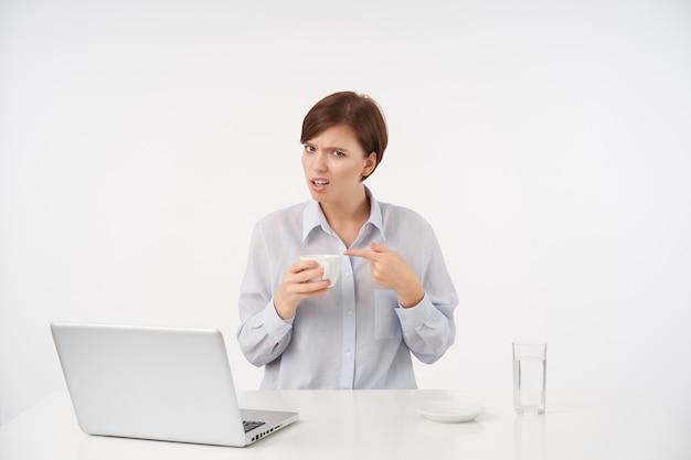 Недовольная молодая симпатичная шатенка с короткой модной стрижкой, держа в руке керамическую чашку и указывая на нее указательным пальцем, смущенно глядя сидя на белом