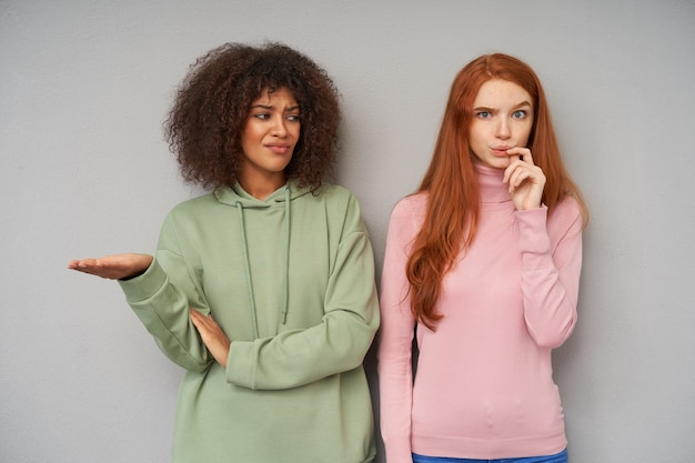 Dissatisfied young pretty dark skinned brunette woman in green hoodie raising confusedly her palm while looking at her lovely bewildered friend with long foxy hair, isolated over grey wall