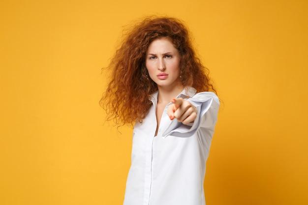 黄色いオレンジ色の壁に孤立したポーズをとってカジュアルな白いシャツを着た不満の若い赤毛の女性の女の子
