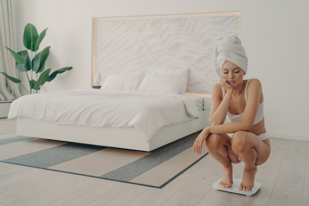 Dissatisfied young shapely woman crouched on scales in stylish light colored bedroom interior at home, wears white classic underwear and towel wrapped on head, daily measuring routine