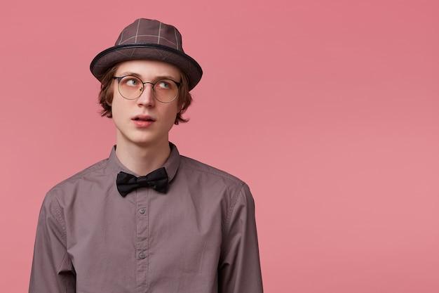 Insoddisfatto giovane ragazzo vestito elegantemente ascolta distrattamente il moralismo dei suoi genitori, si allontana e guarda a destra su uno spazio vuoto di copia, su sfondo rosa