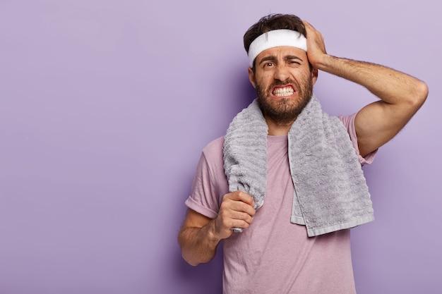 不満のある若いスポーツマンは、運動後に休息し、頭痛で歯を食いしばり、スポーツにうんざりし、肩にタオルを持って立ち、白いヘッドバンドを着用します