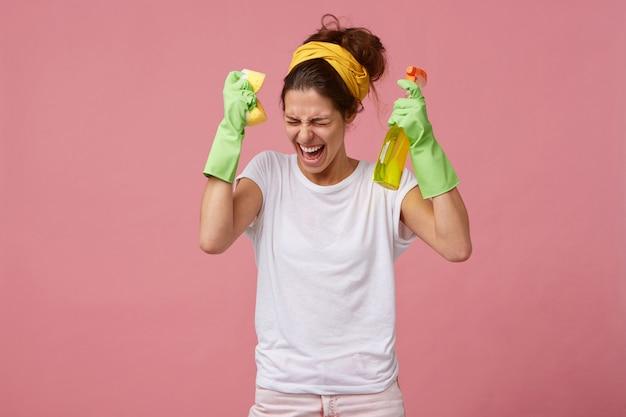 Giovane donna insoddisfatta che tiene una spugna e un detersivo che indossa guanti, fascia gialla sulla testa, non volendo fare le pulizie di casa urlando in preda al panico