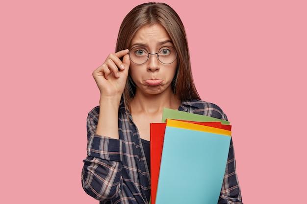 Недовольная молодая женщина позирует на розовой стене в очках
