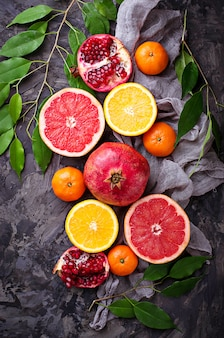 Dissected fresh fruits. pomegranate, orange, grapefruit and tangerines. selective focus